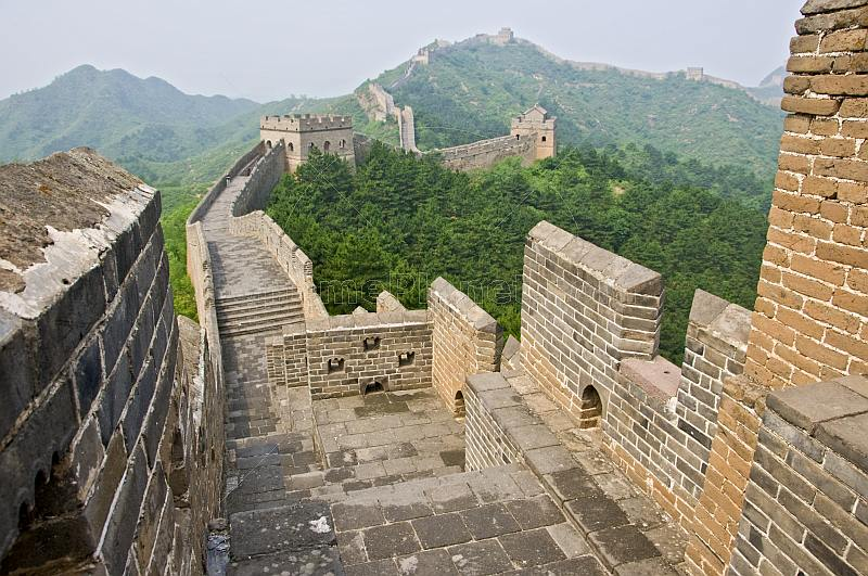 The Great Wall of China crosses forested mountain hillside.