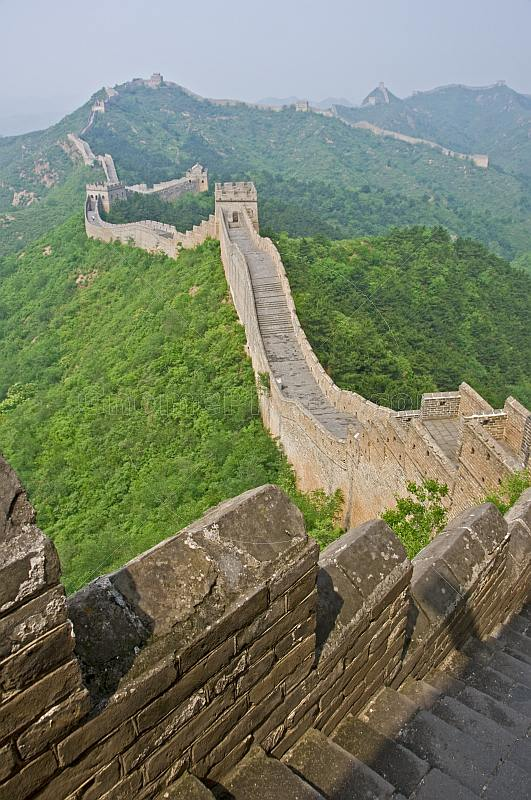 The Great Wall of China crossing forested hills and mountains.