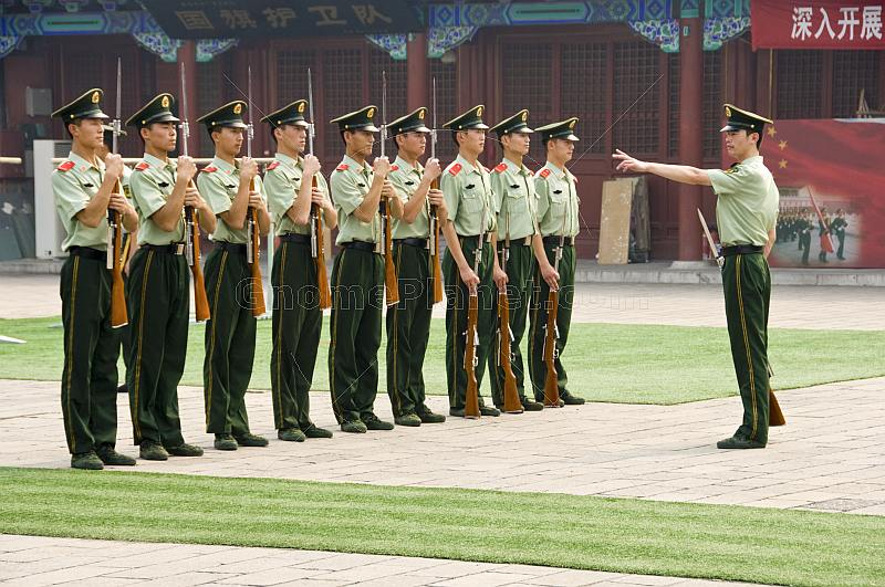 Soldiers with rifles and bayonets on parade in the Forbidden City.