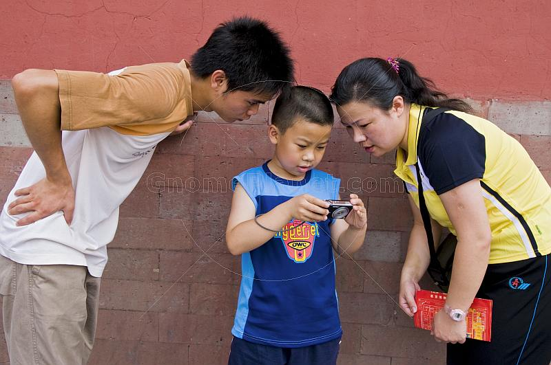 Two Chinese tourists examine their son\\'s digital camera in the Forbidden City.
