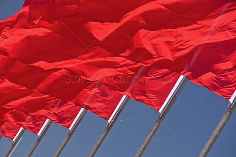 Red flags billowing in the wind of Tiananmen Square.