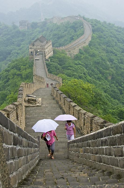 Two Chinese ladies with umbrellas walk along the Great Wall of China.
