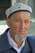Local man with Uighur hat and weather-beaten face.