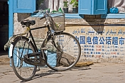 Bicycle parked in the street, next to a wall with Chinese characters.