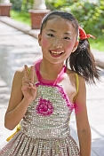 Smiling Chinese girl with party makeup, in sequinned dress.