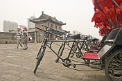 Chinese visitors walk past red and black bicycle rickshaws on the city walls.