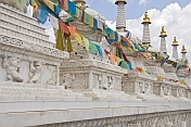 White marble Buddhist stupas draped with prayer flags, at the Dazhao Lamasery.