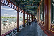Chinese tourists sit in painted colonade at Beihai Lake.