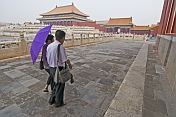 Two Chinese tourists visit the Forbidden City.