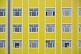 Grid of windows in a yellow and blue apartment building.