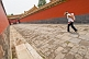 Chinese tourist woman carrying child down a passage to the Imperial Living Quarters in the Forbidden City.