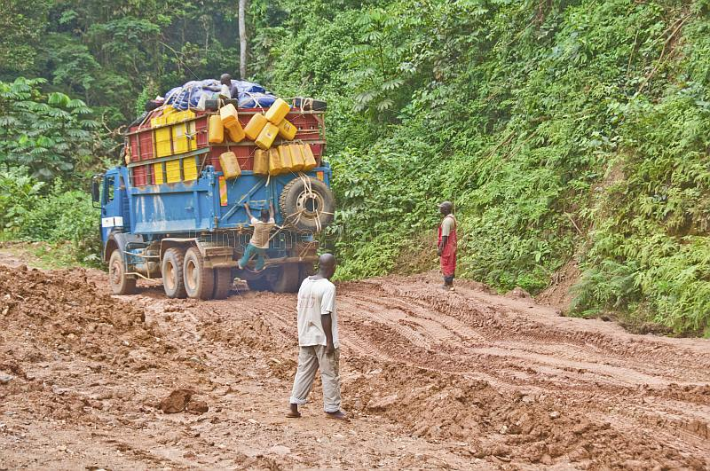 Men watch as heavily laden truck negotiates a muddy section of jungle road.
