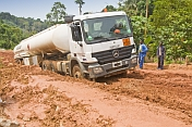 A white fuel tanker struggles to drive along muddy and deeply rutted logging roads.