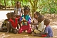 Group of children sit in the shade and play with a plastic doll.