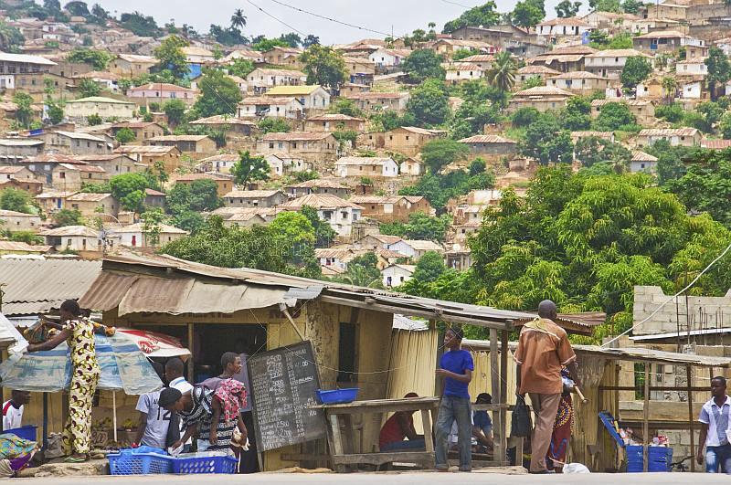 People pass by foodstalls whilst in the background is a hillside covered with brick houses and shacks.