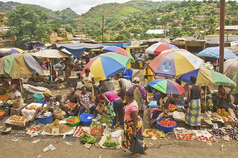 Women under umbrellas selling vegetables in a crowded market with views of hillside to rear.
