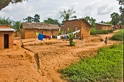 Small children and a line of drying laundry in front of mud-brick shacks and houses.