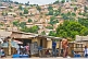 Image of People pass by foodstalls whilst in the background is a hillside covered with brick houses and shacks.