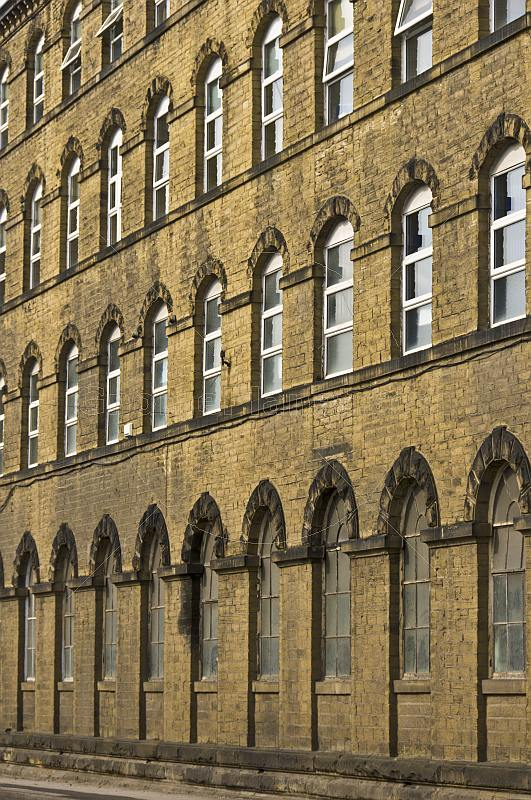 Windows and sandstone wall of old West Yorkshire woolen mill.