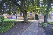 Quaker Meeting House with flagged stone path and beech trees.