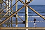 Girl walks on beach under Teignmouth Pier.