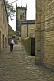 Woman walks up cobbled backstreet towards Holy Trinity Church in Towngate.