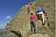 Climbers in red and blue shirts climb the Cow and Calf Rocks on Ilkley Moor.