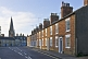 Terraced brick cottages on Olney High Street towards Saint Peter and Saint Paul church.